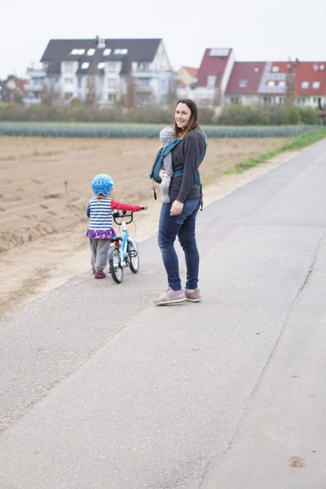 Mama und Töchter - Mama mit Baby in der Trage und Kleinkind mit dem Kinderfahrrad