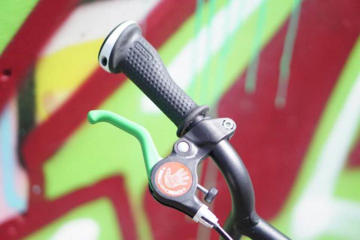 grüne Handbremse und schwarze Handbremse unterscheiden die Vorderrad- und Hinterradbremse - ein Fahrrad für Kleinkinder ab 3 Jahren ist das woom 2 von woombikes mit dem kinder einfach Fahrradfahren lernen können