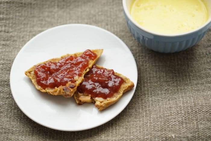 zuckerfreie Marmelade auf einem Brötchen ohne Zucker mit selbstgemachtem Kurkuma Latte. Paste für die goldene Milch selber machen ist ganz einfach.