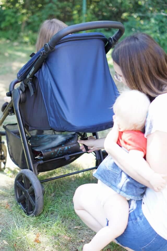Mama und Baby mit Kinderwagen. Liegeposition der Sitzfläche wird eingestellt