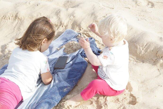 Baby und Kleinkind lieben Musik und tanzen zusammen am Strand. Sandburgen bauen, Muscheln sammeln und das Meer beobachten. Dabei wird Musik von der Playlist für Kinder und schöne Rituale für Kinder mit Deezer gehört