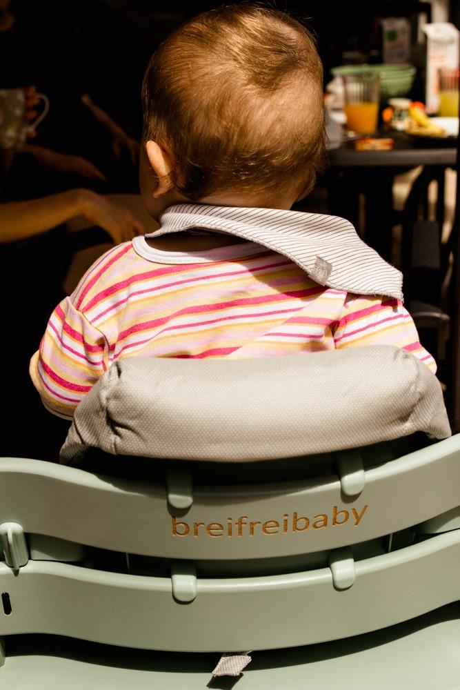 Baby sitzt zum essen im Tripp Trapp